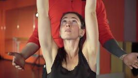 有一位英俊的有用的个人教练员的年轻健康运动的活跃形状女孩在她旁边在健身房 股票视频