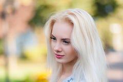 有一俏丽的面孔和美好微笑的美丽的年轻白肤金发的女孩注视 一名妇女的画象有长的头发和惊人的神色的 免版税库存照片
