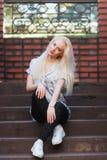 有一俏丽的面孔和美好微笑的美丽的年轻白肤金发的女孩注视 一名妇女的画象有长的头发和惊人的神色的 库存照片