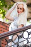 有一俏丽的面孔和美好微笑的美丽的年轻白肤金发的女孩注视 一名妇女的画象有长的头发和惊人的神色的 免版税库存图片