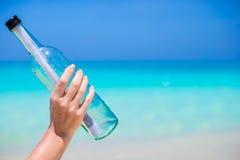 有一则消息的瓶在手背景蓝天 免版税图库摄影