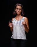 有一剂止痛药的女孩在黑背景的一个胶囊 耐心采取的meds 疾病,憔悴,病症概念 免版税库存图片