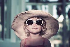 有一副大帽子和大太阳镜的滑稽的白肤金发的小女孩 免版税库存照片