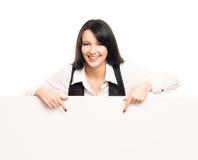 有一副白色空白的横幅的一名愉快的女实业家 库存图片