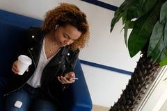 有一副白色耳机的一个美丽的非裔美国人的女孩拿着纸玻璃用咖啡并且调查电话 黑暗 免版税库存图片