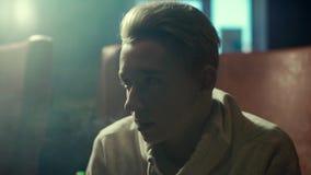 有一副耳环的特写镜头白肤金发的人在他的抽在慢动作的耳朵水烟筒 股票录像