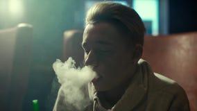 有一副耳环的特写镜头白肤金发的人在耳朵呼气在慢动作的浓烟 股票视频
