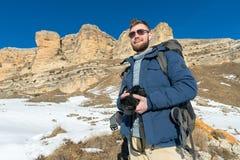 有一副背包和佩带的太阳镜的画象A有胡子的行家摄影师有在他的肩膀的一个大背包的 免版税图库摄影