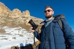 有一副背包和佩带的太阳镜的画象A有胡子的行家摄影师有在他的肩膀的一个大背包的 免版税库存照片