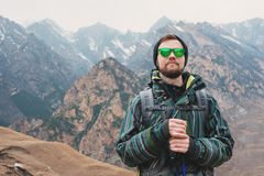 有一副胡子和佩带的太阳镜的在膜夹克,帽子一个人,有一个背包和棍子的北欧走的, a 图库摄影