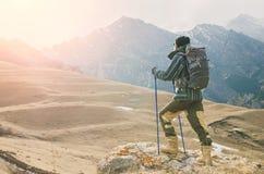 有一副胡子和佩带的太阳镜的在膜夹克,帽子一个人,有一个背包和棍子的北欧走的, a 库存图片