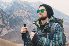 有一副胡子和佩带的太阳镜的在膜夹克,帽子一个人,有一个背包和棍子的北欧走的, a 免版税图库摄影