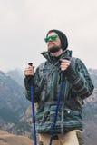 有一副胡子和佩带的太阳镜的在膜夹克,帽子一个人,有一个背包和棍子的北欧走的, a 免版税库存图片