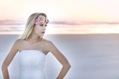 有一副花卉戴头受话器的一名美丽的白肤金发的妇女在站立在日出的海滩 图库摄影