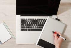 有一副铅笔图的女性手在一个图形输入板,在底下膝上型计算机 免版税库存照片