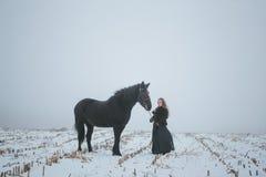 有一匹马的一个女孩在一个领域在冬天 免版税图库摄影