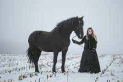 有一匹马的一个女孩在一个领域在冬天 库存图片