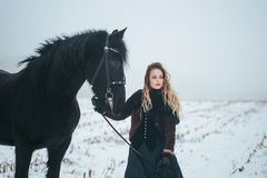 有一匹马的一个女孩在一个领域在冬天 免版税库存图片