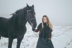 有一匹马的一个女孩在一个领域在冬天 库存照片