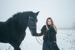 有一匹马的一个女孩在一个领域在冬天 免版税库存照片