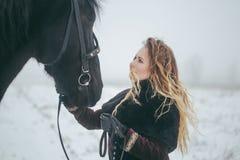 有一匹马的一个女孩在一个领域在冬天 图库摄影