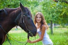 有一匹马的女孩在庭院里。 图库摄影