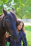 有一匹马的女孩在庭院里。 库存照片