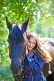 有一匹马的女孩在庭院里。 免版税库存照片