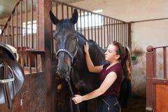 有一匹马的女孩在槽枥 免版税图库摄影