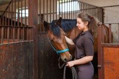有一匹马的女孩在槽枥 免版税库存图片
