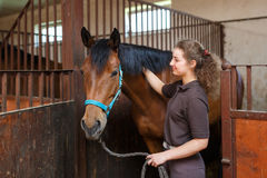 有一匹马的女孩在槽枥 图库摄影