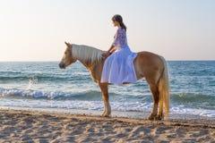 有一匹马的女孩在海滩 库存图片