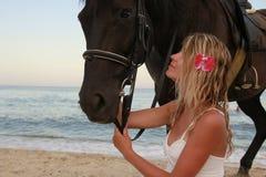 有一匹马的女孩由海 免版税库存图片