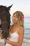 有一匹马的女孩由海 免版税库存照片