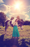 有一匹马的美丽的妇女在领域 一个农场的女孩有a的 库存图片