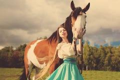 有一匹马的美丽的妇女在领域 一个农场的女孩有a的 免版税库存照片