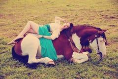 有一匹马的美丽的妇女在领域 一个农场的女孩有a的 库存照片
