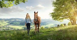 有一匹马的美丽的白肤金发的女孩在美妙的风景 免版税库存图片