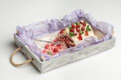 有一半的木盘子被吃的可口蛋白甜饼蛋糕用在白色背景的果子 图库摄影