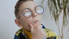 有一双美好的微笑和蓝眼睛的传神矮小的7-8year孩子与玻璃考虑一个有趣的想法 股票录像