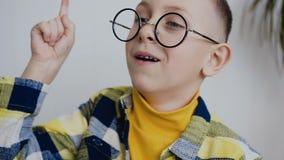有一双美好的微笑和蓝眼睛的传神矮小的7-8year孩子与玻璃考虑一个有趣的想法 股票视频