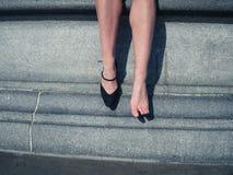 有一双鞋子的妇女在城市 免版税库存图片