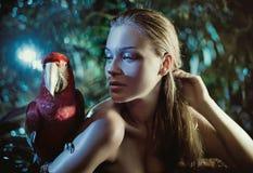 有一只五颜六色的鹦鹉的肉欲的妇女 图库摄影