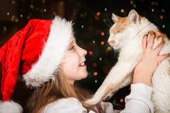 有一只喜爱的猫的愉快的小女孩在圣诞节 免版税库存照片