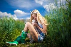 有一只小山羊的国家女孩在她的手上 库存图片