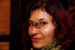 有一只小橙色蝴蝶的女孩坐她的面孔 免版税库存照片