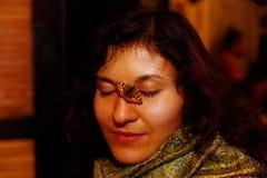 有一只小橙色蝴蝶的女孩坐她的面孔 免版税图库摄影