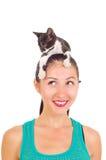 有一只小猫的美丽的微笑的女孩在她的头 免版税库存照片