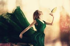 有一只小蝴蝶的美丽的妇女 免版税库存照片