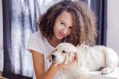 有一只小金毛猎犬的少年女孩 免版税库存图片